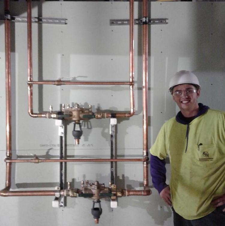 Technician next to piping
